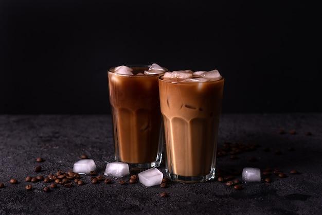 背の高いグラスにアイスコーヒーを注ぎ、クリームを注ぎます。ウッドの背景。低いキー。