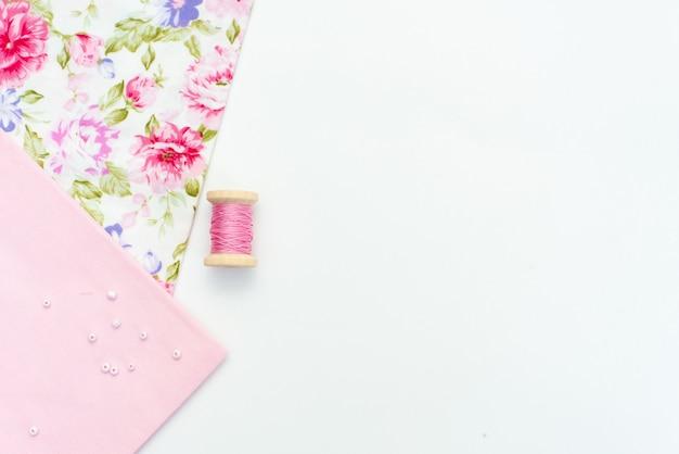 ピンクの天然布と白い木製のテーブルの上の裁縫用具