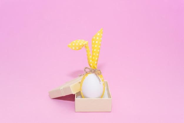 Белое пасхальное яйцо с ушками зайчика на розовом фоне