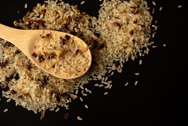 米と木のスプーンで黒の背景
