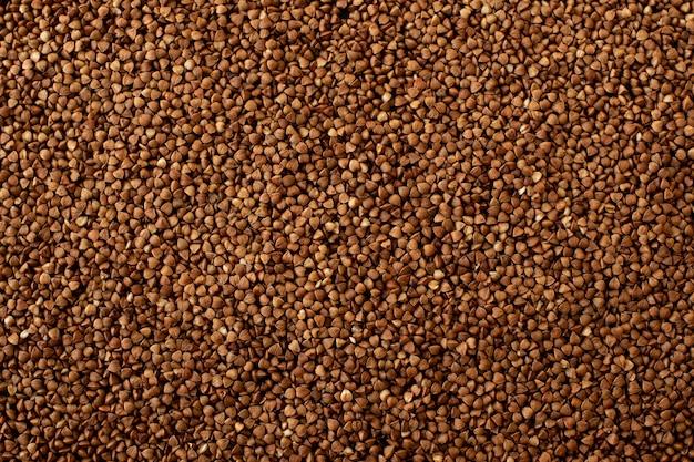 茶色の木製のテーブルの上の木のスプーンでそばの種