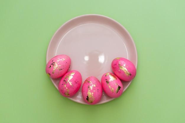 黄金のイースターのフレームは、パステル調の緑の背景に卵を装飾されています。