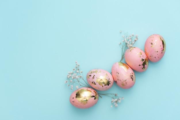 黄金のイースターのフレームは、パステル調の青い背景に卵を飾った。
