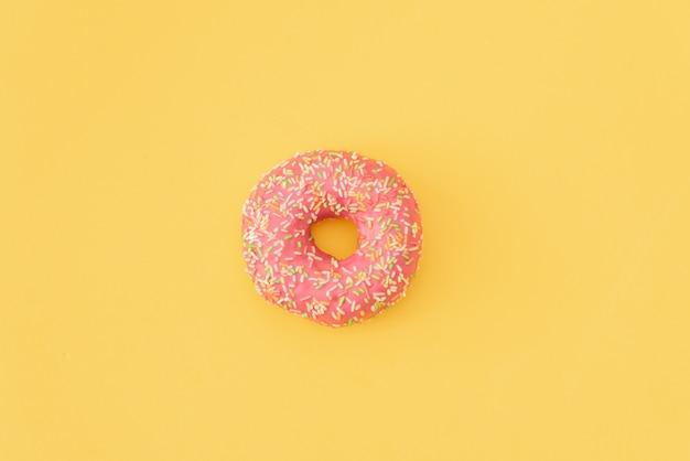 ピンクの背景に落ちる動きで様々な装飾ドーナツ。甘くてカラフルなドーナツが落下したり、飛んでいます。
