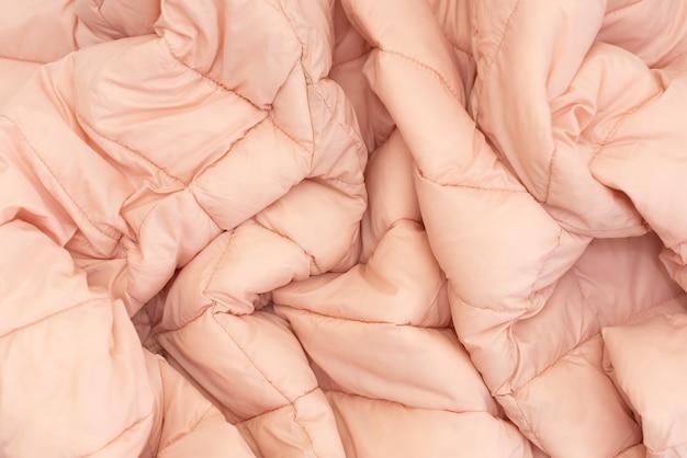 ダウンジャケット生地の背景、ピンクのフグジャケットの質感