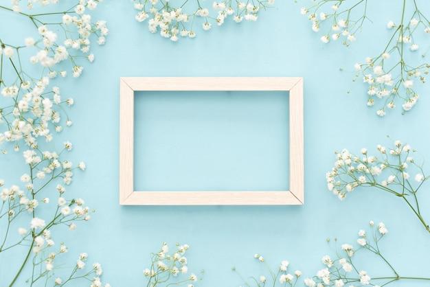 ロマンチックな花の組成。白い石膏の花、パステル調の青い背景上のフォトフレーム。