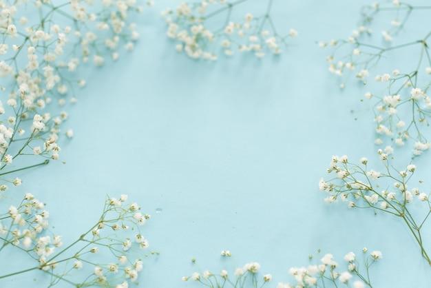 上から青い背景に結婚式の花のフレーム。美しい花柄。平干しスタイル。