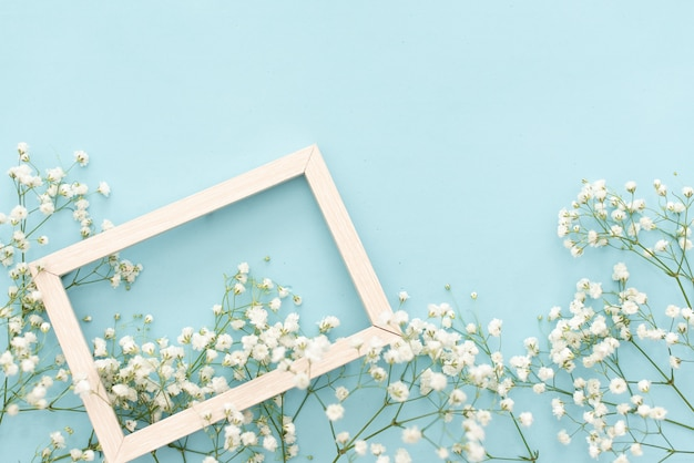 Композиция цветов романтическая. цветы белые гипсофилы, фото рамка на пастельных синем фоне.