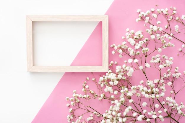 ロマンチックな花の組成。白い石膏花、パステル調のピンクの背景のフォトフレーム。