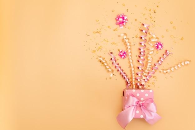 Желтая подарочная коробка с различными партийными конфетти, растяжками, шумоглушителями и украшениями на оранжевом фоне