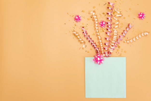 風船と誕生日上面の紙吹雪からフレームとパステルピンクのテーブル。フラットレイ構成。