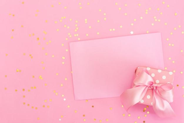 ピンクの背景の封筒にピンクのかぎ針編みの心。バレンタインデーのロマンチックなお祝い。