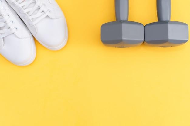 Фитнес-аксессуары на желтом фоне. кроссовки, бутылка воды, наушники и гантели.