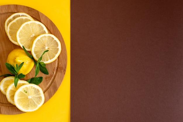 Нарезанный желтый лимон на коричневой деревянной доске, рядом с ним лежит пучок зеленой мяты, летние напитки