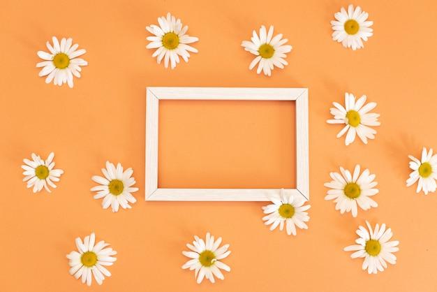 Цветочный узор с мелкими цветочками ромашки, листьями и лепестками на синей модной пастели