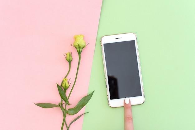携帯電話、シルク、人工綿花の枝を持つ女性の指のフラットレイアウトの概念。