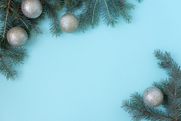 クリスマスまたは冬の組成。雪の結晶とパステルブルーの背景に赤い果実のフレーム。クリスマス、冬、新年のコンセプト。フラット横たわっていた、トップビュー、コピースペース