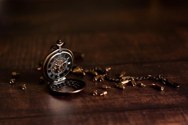 ヴィンテージの懐中時計と砂時計または砂時計、コピースペースで時間のシンボル