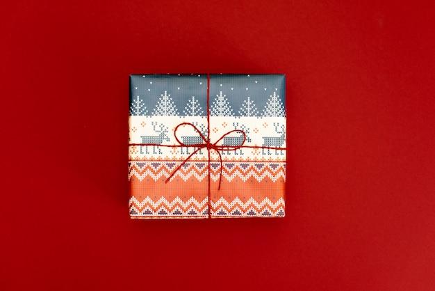 クリスマスプレゼントは赤の背景に提示します。シンプルでクラシックな赤と白のラップギフトボックスにリボン弓とホリデーホリデーデコレーション。