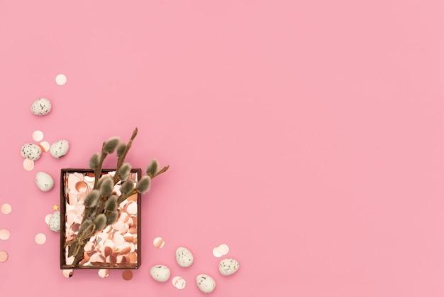 ピンクの背景の党吹流しでイースターエッグを装飾しました。イースターのコンセプトです。平らに置きます。