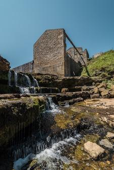 古い台無しにされた工場と川の滝