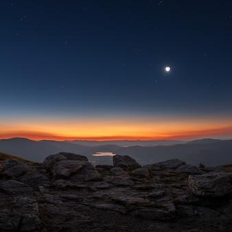 スペインの中心部の山々から三日月とトワイライトの日の出