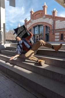 Инвалид молодой человек в инвалидной коляске падает с лестницы
