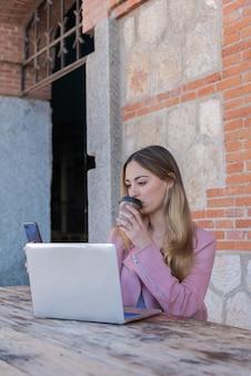 若い女性が彼女のラップトップと携帯電話を路上で木製のテーブルに座っての作業