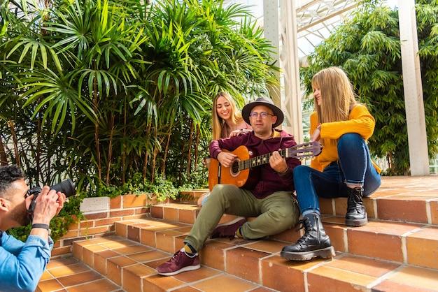 Две девушки улыбаются, а музыкант играет на гитаре