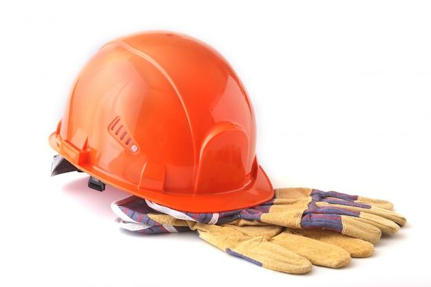 オレンジ色のヘルメット、白い背景の上の安全手袋。安全ヘルメット