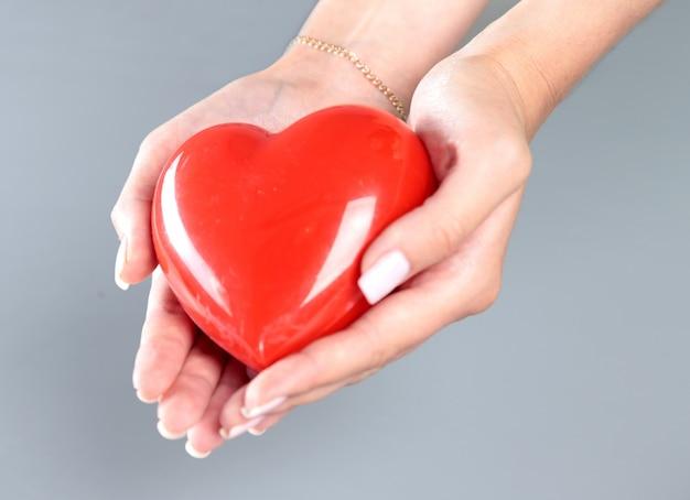 Доктор молодой женщины держа красное сердце
