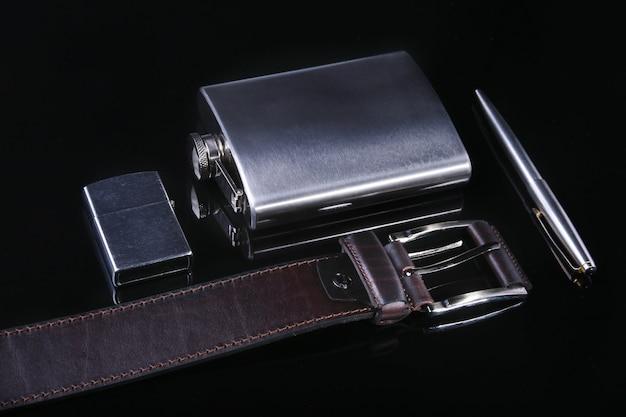 ステンレスヒップフラスコ、ライター、ペン、高級ベルトミラーブラックの背景に分離されました。
