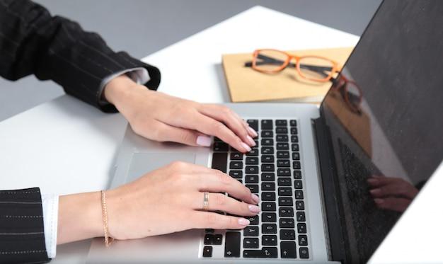 キーボードで女性の手を入力することのクローズアップ
