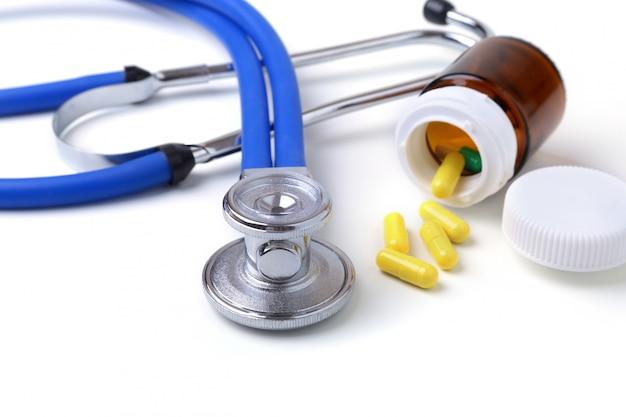 Ассорти таблетки и стетоскоп на белом фоне.