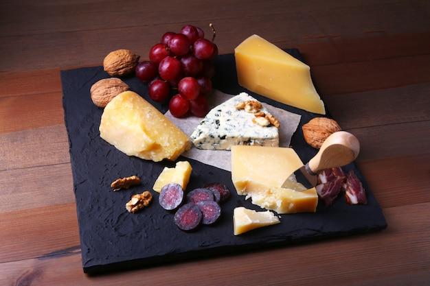 木製のサービングトレイ上のフルーツ、ブドウ、ナッツ、チーズナイフとチーズの品揃え。