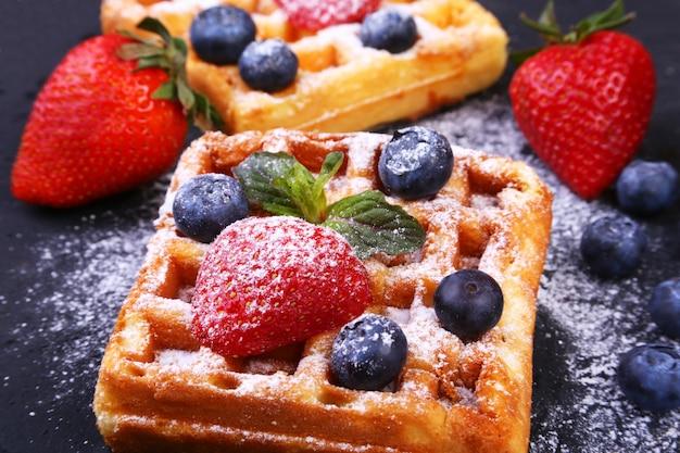 自家製の伝統的なベルギーワッフル、新鮮なフルーツ、ベリー、ブラックプレートに砂糖の粉。