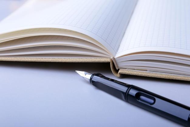 デスクトップ上のビジネスアクセサリー:ノート、日記、万年筆、メガネ。