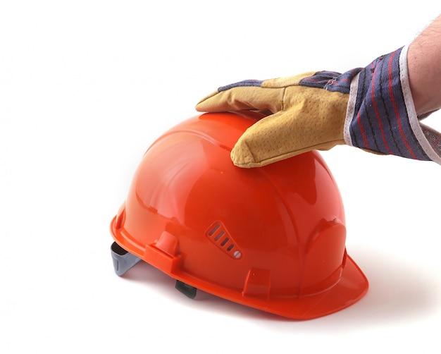 保護手袋の労働者は彼の手でオレンジ色のヘルメットを保持しています。
