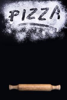 碑文のピザ、麺棒、黒いテーブルの上に小麦粉とバナー。テキスト用の空き領域を持つ背景。