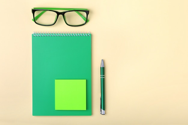 Деловые аксессуары на рабочем столе: блокнот, дневник, перьевая ручка, очки.