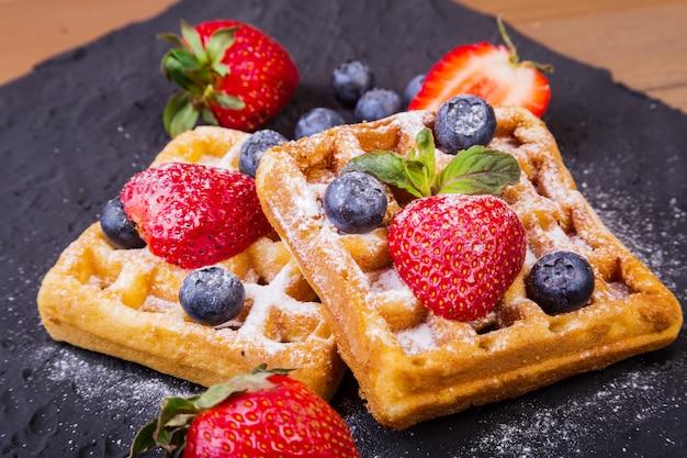 自家製の伝統的なベルギーワッフル、新鮮なフルーツ、ベリー、ブラックプレートに砂糖の粉。平干し、