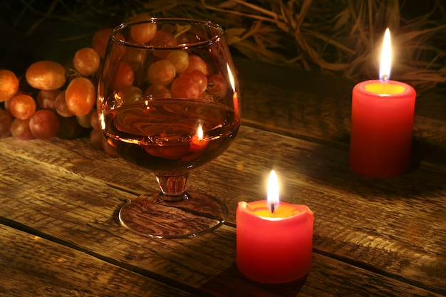 クリスマスキャンドル、ブドウ、コニャックまたはウイスキーとグラス