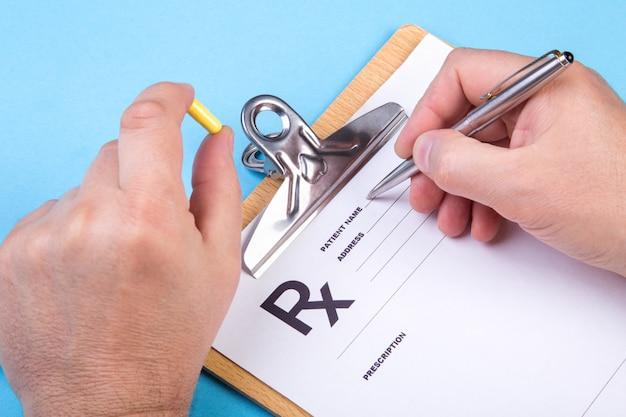 医者または薬剤師が瓶または薬の瓶を手で押し、特別なフォームに処方箋を書きます。医療費と医療費の支払いの概念。