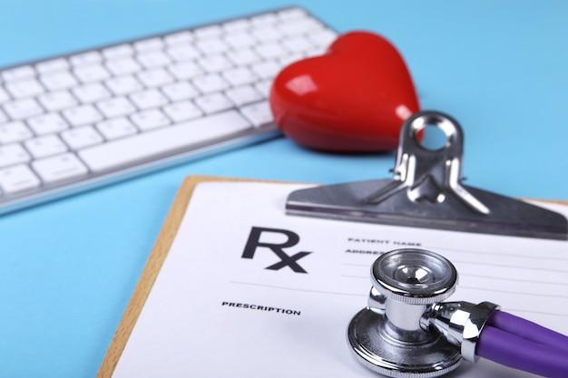 医療聴診器と心電図グラフのクローズアップの上に横たわる赤いハート。医療支援、予防、病気の予防または保険の概念。循環器ケア。