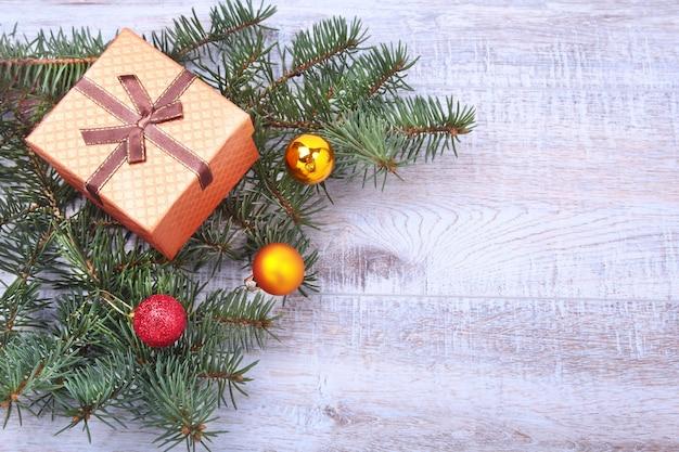 ギフト用の箱、カラフルなボール、木製のデスクトップ上のクリスマスツリーとクリスマスの装飾。