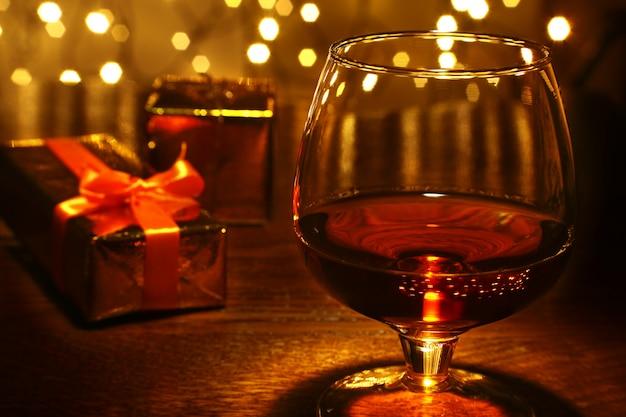木製のテーブルにウイスキー、コニャック、ブランデー、ギフトボックス。光のお祝い組成