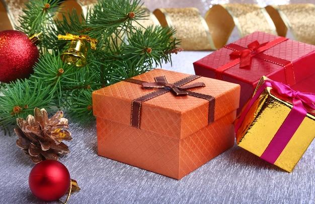 Новогоднее украшение с подарочными коробками, разноцветными елочными шарами, елкой и шишками на размытом, сверкающем и сказочном