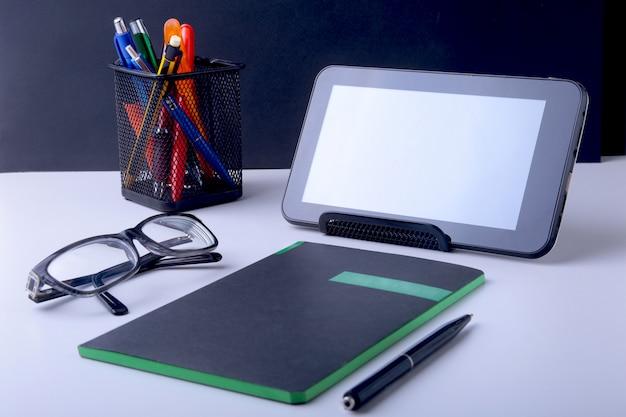 ラップトップ、スマートフォン、その他の備品を備えたモダンな白いオフィスデスクテーブル。中央にテキストを入力するための空白のノートブックページ。