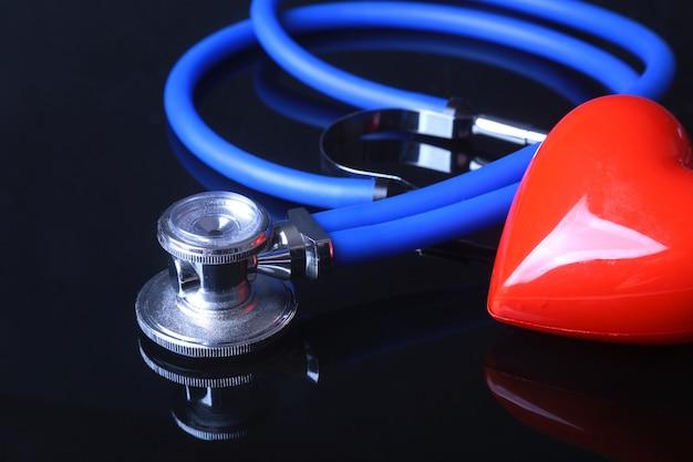 Стетоскоп, красное сердце и метр кровяного давления на черном фоне зеркала.