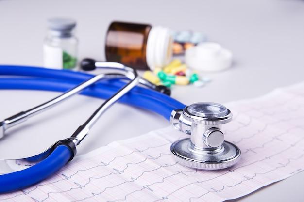 薬と心電図の上に横たわる医療聴診器のボトル